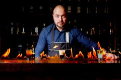 Exposition ardente à la barre Le barman fait le cocktail alcoolique chaud et met à feu la barre Le barman prépare un cocktail ard photo stock