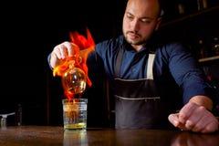 Exposition ardente à la barre Le barman fait le cocktail alcoolique chaud et met à feu la barre Le barman prépare un cocktail ard photos stock