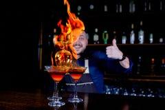 Exposition ardente à la barre Le barman fait le cocktail alcoolique chaud et met à feu la barre Le barman prépare un cocktail ard photographie stock libre de droits