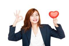 Exposition asiatique de femme d'affaires un coeur rouge et un signe CORRECT Images stock