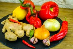 Exposition close up of fresh organic vegetables, composition with assorted raw organic vegetables, red pepper, onion and garlic, g. Reen pepper and red hot chili Stock Images