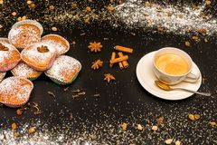 Exposition of cupcake with cup of coffee, cinnamon and sugar on black table, very tasty cakes for any celebration. Royalty Free Stock Photography