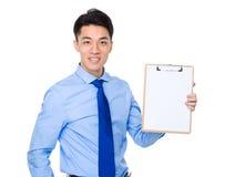 Exposition d'homme d'affaires avec la page vide du presse-papiers Photo stock