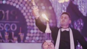 Exposition de barman au restoran de partie de disco, barman de professionnel de jeune homme Bouteilles de jonglerie de barman mas clips vidéos