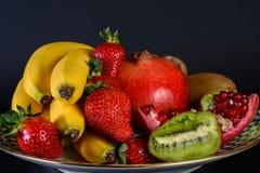 Exposition de fruit naturel frais, de fraise organique, de moitié de grenat, de banane et de kiwi du plat russe de porcelaine de  Image stock