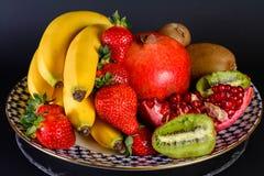 Exposition de fruit naturel frais, de fraise organique, de moitié de grenat, de banane et de kiwi du plat russe de porcelaine de  Images stock