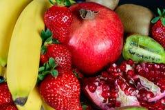 Exposition de fruit naturel frais, de fraise organique, de moitié de grenat, de banane et de kiwi, fond noir, nourriture saine, Image libre de droits