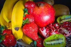 Exposition de fruit naturel frais, de fraise organique, de moitié de grenat, de banane et de kiwi, fond noir, nourriture saine, m Photos stock