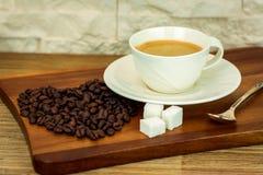 Exposition de la tasse de café blanche avec du sucre et des grains de café sur la table en bois et le fond blanc de mur de brique Image libre de droits