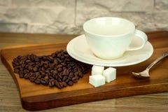 Exposition de la tasse de café blanche avec du sucre et des grains de café sur la table en bois et le fond blanc de mur de brique Images libres de droits