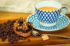 Exposition de tarte de caramel près de la tasse de café blanche avec du sucre et des grains de café sur la table en bois et le fo Photographie stock libre de droits