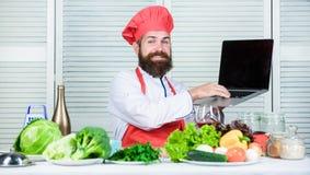 Exposition de TV Homme barbu heureux recette de chef Salade v?g?tarienne avec les l?gumes frais Aliment biologique suivant un r?g photographie stock libre de droits