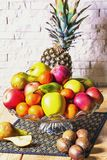 Exposition of fresh fruits, pineapple, green and red apple, kiwi, mandarin, pear on wooden table and white brick wall background,. Organic fruits stock photo