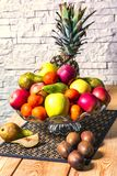 Exposition of fresh fruits, pineapple, green and red apple, kiwi, mandarin, pear on wooden table and white brick wall background,. Organic fruits stock photos