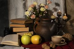 Exposition of hand made clay set on white wooden table, with books, candles, flowers, apple. Tea cup and clay kettle. Vintage styl
