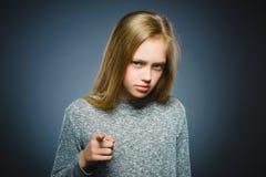 Exposition réfléchie ou méprisante de plan rapproché de fille à l'appareil-photo d'isolement sur le gris images libres de droits