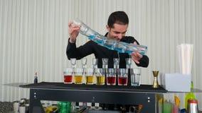 Exposition tenante le bar avec le barman versant les tirs alcooliques multiples de cocktails banque de vidéos