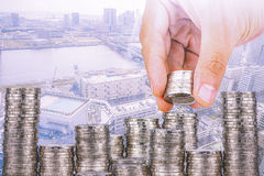 Exposure of Finance and Saving money banking concept,Hope of investor concept,Male hand putting money coin like stack growing busi. Ness. background the city Royalty Free Stock Image