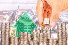 Exposure of Finance and Saving money banking concept,Hope of investor concept,Male hand putting money coin like stack growing busi. Ness. background the city Royalty Free Stock Images