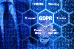 IT exppert touching a tile in a grid with GDPR keywords Stock Photo