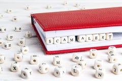 Exprese la alarma de Scam escrita en bloques de madera en cuaderno rojo en wh Imágenes de archivo libres de regalías