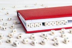 Exprese la fábrica del riesgo escrita en bloques de madera en cuaderno rojo encendido Imagen de archivo