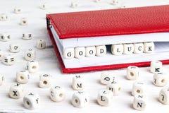 Exprese la suerte de Cood escrita en bloques de madera en cuaderno rojo en whi Fotografía de archivo
