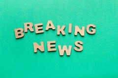 Exprese las noticias de última hora hechas de letras de madera en fondo verde Imagen de archivo