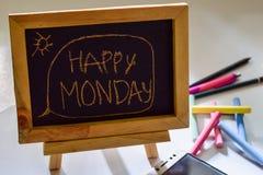 Exprese lunes feliz escrito en una pizarra en ella y el smartphone, tiza colorida imagen de archivo