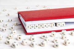 Exprese nos entran en contacto con escritos en bloques de madera en cuaderno rojo en wh Fotografía de archivo libre de regalías