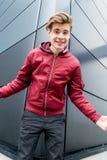 Expresión adolescente del muchacho de la alegría y de la felicidad que se colocan delante de fondo urbano Foto de archivo