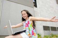 Expresión adolescente triguena hermosa con la computadora portátil Fotos de archivo