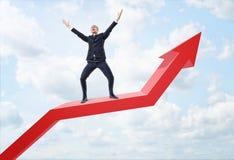 Expresión del hombre de negocios feliz y situación en la línea gráfico roja grande con una flecha vuelta hacia arriba foto de archivo libre de regalías