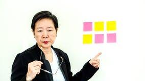 Expresión infeliz de la mujer mayor asiática del negocio con el espacio n de la copia Foto de archivo libre de regalías