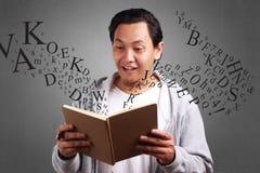Expresión sorprendida del libro de lectura del hombre joven imagenes de archivo