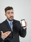 Expresión divertida del hombre de negocios joven que muestra la pantalla rota del teléfono móvil Foto de archivo libre de regalías