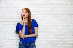 Expresiones faciales de la mujer joven del pelirrojo en la pared de ladrillo Foto de archivo libre de regalías