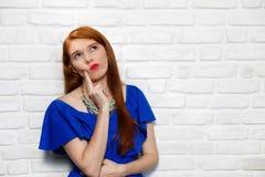 Expresiones faciales de la mujer joven del pelirrojo en la pared de ladrillo Fotografía de archivo libre de regalías