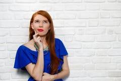 Expresiones faciales de la mujer joven del pelirrojo en la pared de ladrillo Fotos de archivo libres de regalías