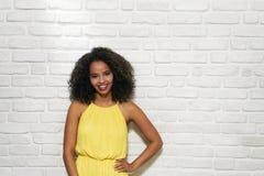 Expresiones faciales de la mujer negra joven en la pared de ladrillo Foto de archivo