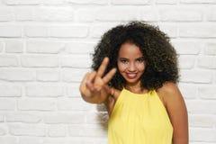 Expresiones faciales de la mujer negra joven en la pared de ladrillo Imagenes de archivo