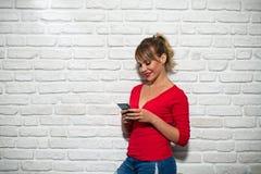 Expresiones faciales de la mujer rubia joven en la pared de ladrillo Fotografía de archivo libre de regalías
