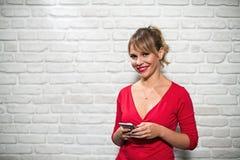 Expresiones faciales de la mujer rubia joven en la pared de ladrillo Imagen de archivo libre de regalías