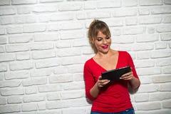Expresiones faciales de la mujer rubia joven en la pared de ladrillo Fotos de archivo libres de regalías