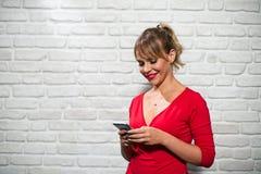 Expresiones faciales de la mujer rubia joven en la pared de ladrillo Fotos de archivo