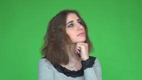 Expresiones y emociones de la cara La mujer bonita joven pensativa que lleva a cabo la mano bajo su cabeza está pensando metrajes
