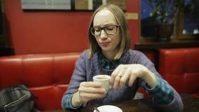 Expressão facial da emoção negativa A moça com vidros é infeliz com seu café e é insultada e quer a vídeos de arquivo