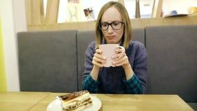 Expressão facial da emoção negativa A moça com vidros é infeliz com seu chá e é insultada e quer a vídeos de arquivo