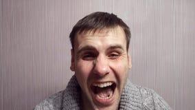 A expressão facial das mudanças do ator, homem irritado torna-se amável, a agressão é substituída pelo riso e então para trás video estoque