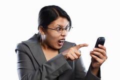 Expressão irritada da mulher de negócios usando o atendimento video imagem de stock